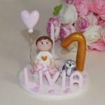 Figurine petite fille tenant un ballon coeur et son doudou lapin