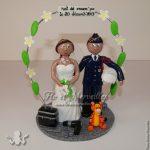couple de figurines avec mariée en robe de mariage, marié en tenue de gendarme, une peluche Tigrou et une arche de frangipanier