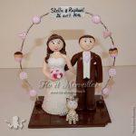 Couple de figurines en tenue de mariage, avec arche de pâtisserie