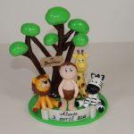 Figurine enfant dans la savane, avec un lion, une girafe et un zèbre