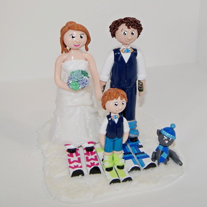 couple de mariés avec enfant et chat, sur skis, socle enneigé