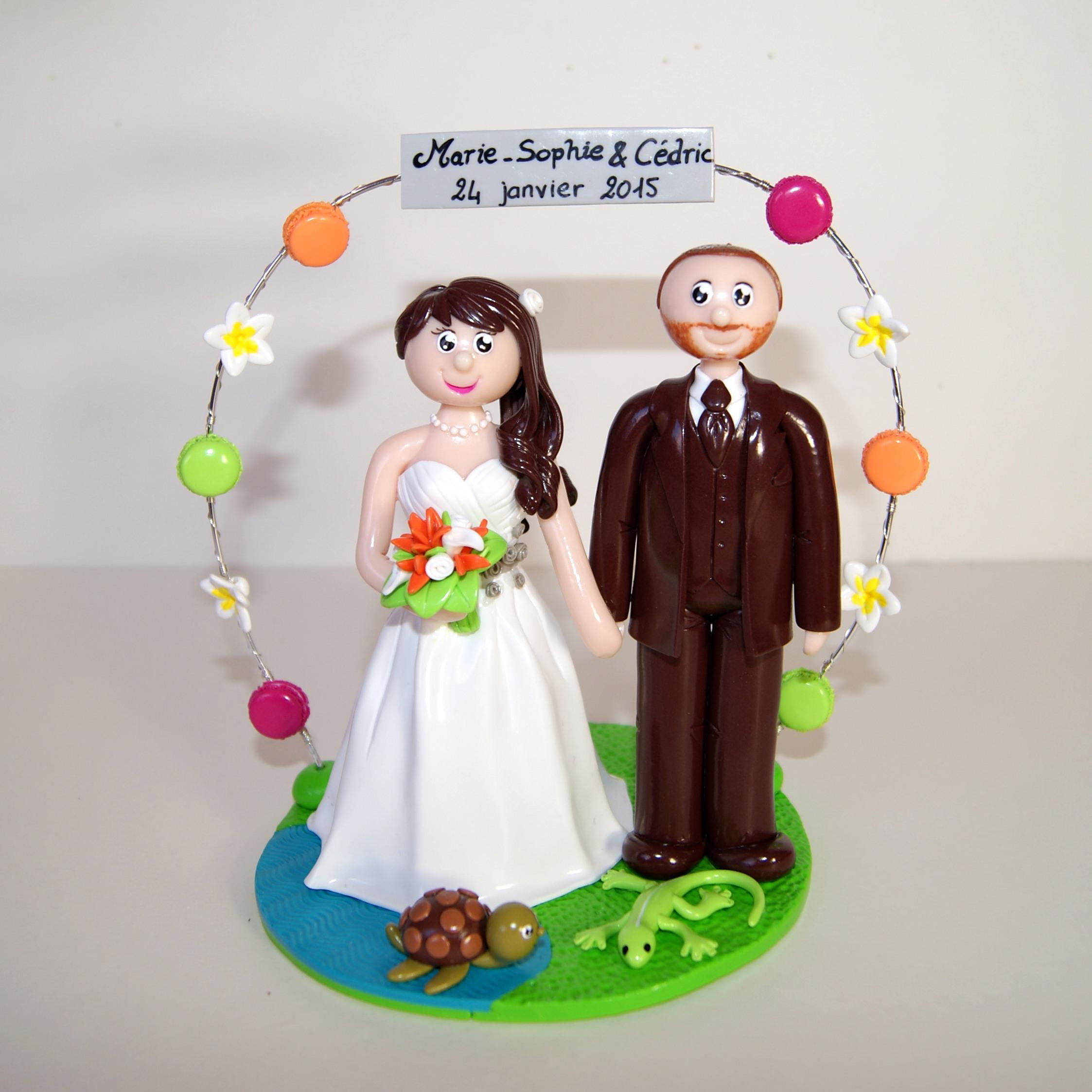 Figurines de couples de mariés, avec petite tortue et petit margouillat, arche de macarons et de fleurs de frangipanier