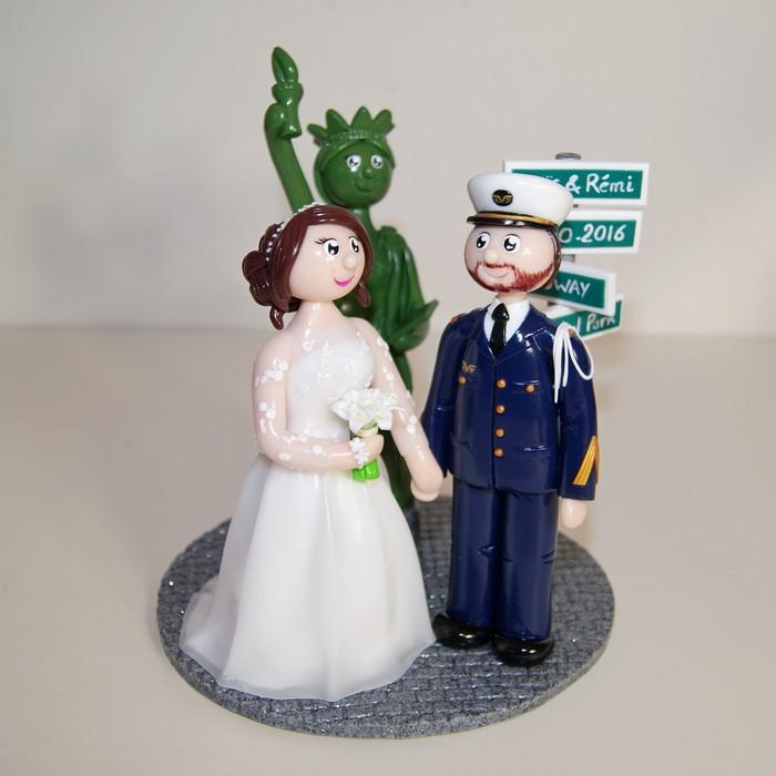 Figurines de mariage avec mariée en robe de mariage, marié en uniforme de l'armée, devant la Statue de la Liberté, New York