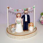 figurine de mariage personnalisées, avec deux enfants, sur socle en bois brut, banderole de fanions