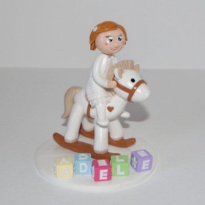 figurine enfant à califourchon sur un cheval à bascule, cubes lettres prénom