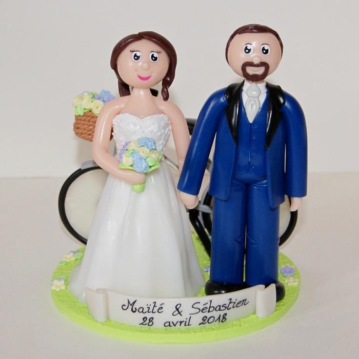Figurines en tenue de mariage, vélo en arrière-plan avec panier rempli de fleurs champêtres