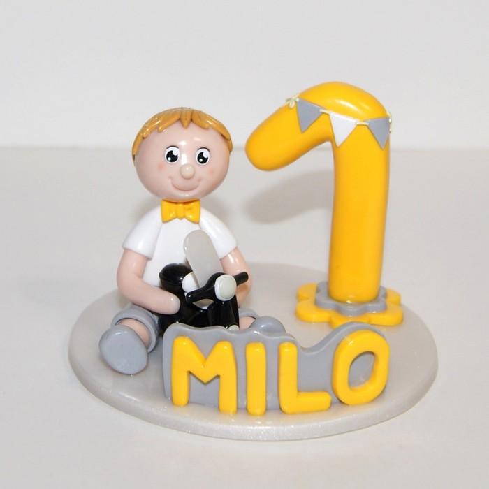 Figurine anniversaire 1 an de Milo, jaune et gris, tenant un vespa dans les mains.