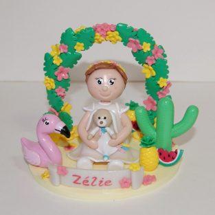 Figurine baptême, petite fille tenant son doudou, sur le thème tropical, avec flamant rose, cactus, ananas et pastèque